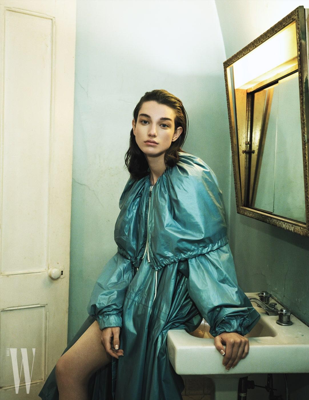 어깨가 덮이는 넓은 칼라의 하늘색 원피스 겸 코트는 Calvin Klein 205W39NYC 제품.