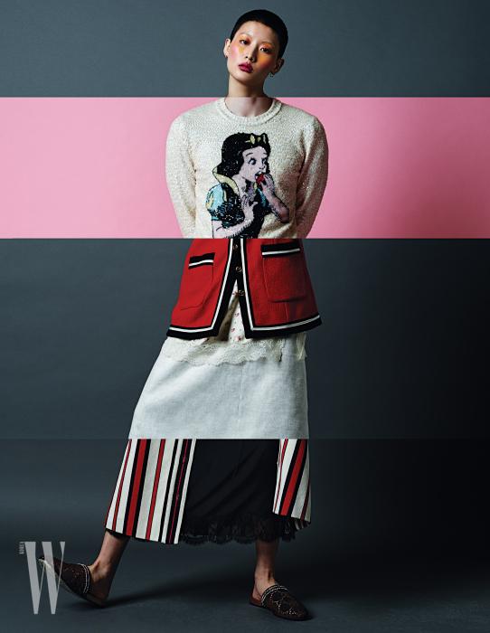 남성 컬렉션의 디즈니 백설 공주 모티프 비즈 장식 스웨트 셔츠, 여성 컬렉션의 레이스 장식 튜닉과 그래픽적인 붉은색 카디건, 여성 컬렉션의 레이스 장식 검정 드레스와 줄무늬 롱스커트, 벨벳 슬리퍼는 모두 구찌 제품.