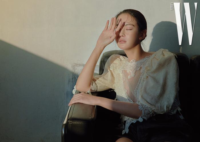 레이스 장식 블라우스와 가죽 쇼츠는 생로랑 by 안토니 바카렐로 제품.