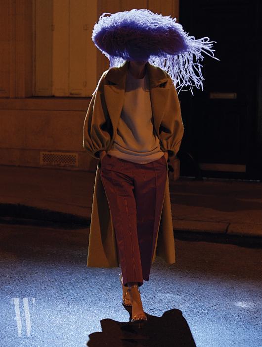 겨자색 코트와 인디언 핑크색 팬츠, 안에 입은 톱, 스트랩 샌들, 거대한 깃털 모자는 모두 Valentino Couture 제품.