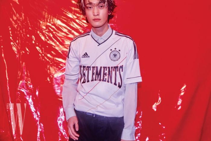 축구 유니폼은 Nss Magazine, 안에 입은 시스루 셔츠와 검은색 팬츠는 Berluti, 스트랩 벨트는 Louis Vuitton 제품.