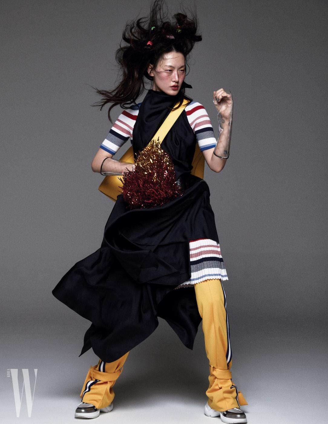 구조적인 실루엣의 검정 실크 드레스는 Celine, 줄무늬 니트 드레스는 Tommy Jeans, 팬츠는 YCH, 가방은 Calvin Klein Jeans Accessories, 투명 장갑은 Chanel, 스니커즈는 Louis Vu itton 제품.