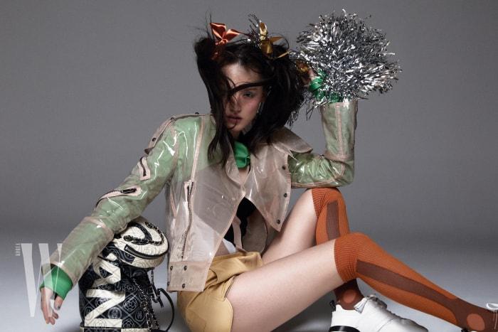 PVC 재킷은 Valentino, 재킷 안에 입은 연두색 볼레로는 YCH, 그래픽 무늬 보디슈트는 Bottega Veneta, 가죽 쇼츠는 Bally, 타이츠는 Miu Miu, 스니커즈는 Tod's, 스포티 가방은 Chanel 제품 .