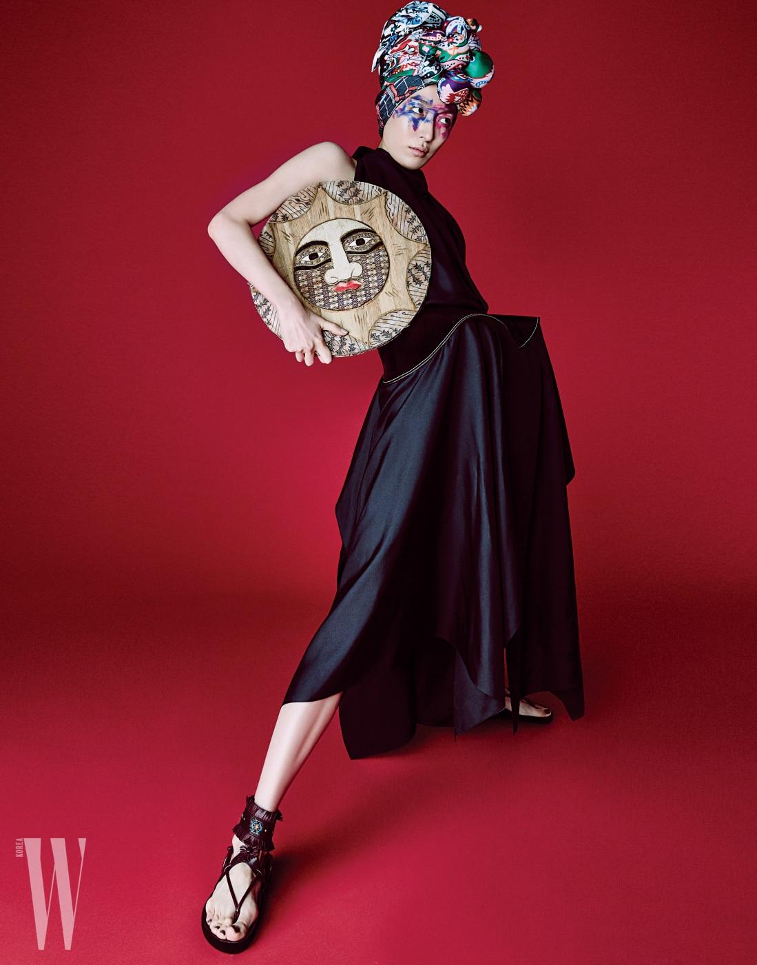 구조적인검정 드레스는Celine, 에스닉한샌들은Isabel Marant, 터번으로연출한화려한패턴의스카프는Hermes, Kenzo, Valentino Garavani 제품.