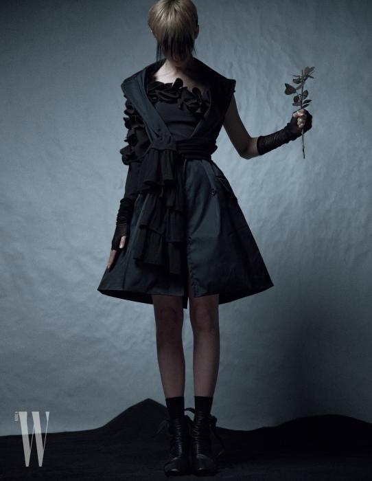 입체적으로 꽃잎을 장식한 원숄더 드레스는 21 Defaye, 베스트 재킷은 Prada, 허리에 묶은 스웨터는 Michael Michael Kors, 검은색 신발은 Celine 제품.