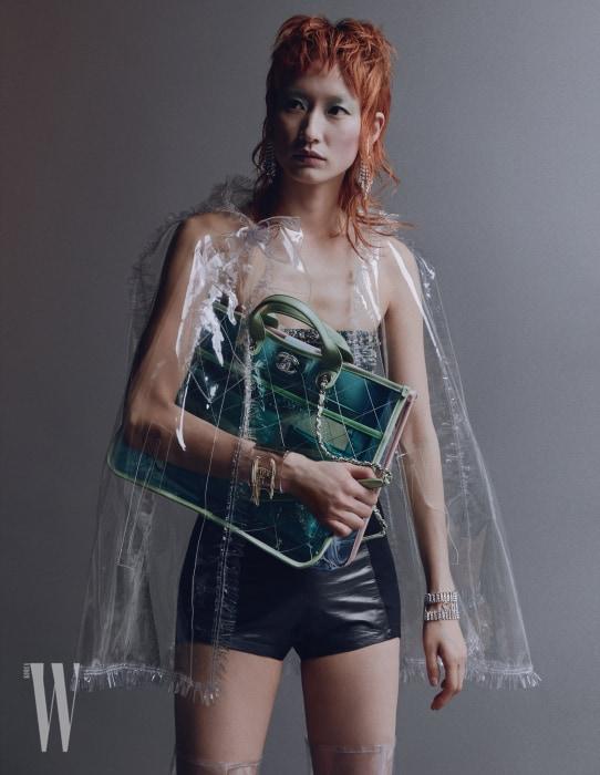 PVC와 램스킨 소재의 쇼퍼백, 투명한 러플 장식 케이프, 트위드 톱, 귀고리, 뱅글, 팔찌, 부츠는 모두 Chanel 제품. 가죽 쇼츠는 스타일리스트 소장품.