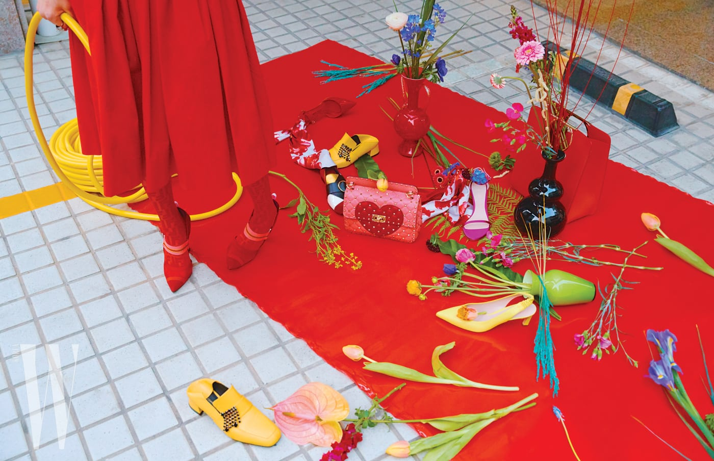 메탈 반지는 Vivienne Westwood, 붉은색 스커트와 F 로고 장식 타이츠, 밴딩 장식의 힐은 모두 Fendi 제품. 바닥에 놓인 스카프 장식의 붉은색 페이턴트 힐은 Salvatore Ferragamo, 검정 스톤 소재의 프린지 장식이 돋보이는 노란색 로퍼는 Stuart Weitzman, 컬러 블록 패턴이 돋보이는 로퍼는 Bally, 하트 모티프의 스터드 장식 백은 Valentino Garavani, 보라색 새틴 소재 스트랩 힐과 레몬색 슬링백 슈즈는 Stuart Weitzman 제품.