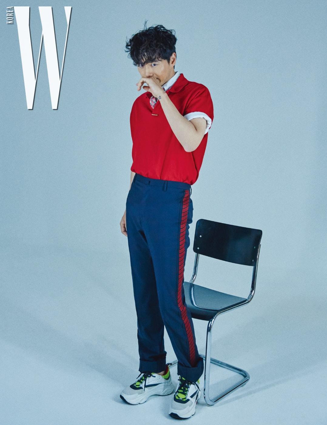 빨강 피케 셔츠와 안에 입은 셔츠, 핑크색 타이는 스타일리스트 소장품, 빨 강 라이닝이 들어간 팬츠는 Lanvin by Boontheshop, 스니커즈는 Dior 제품 .