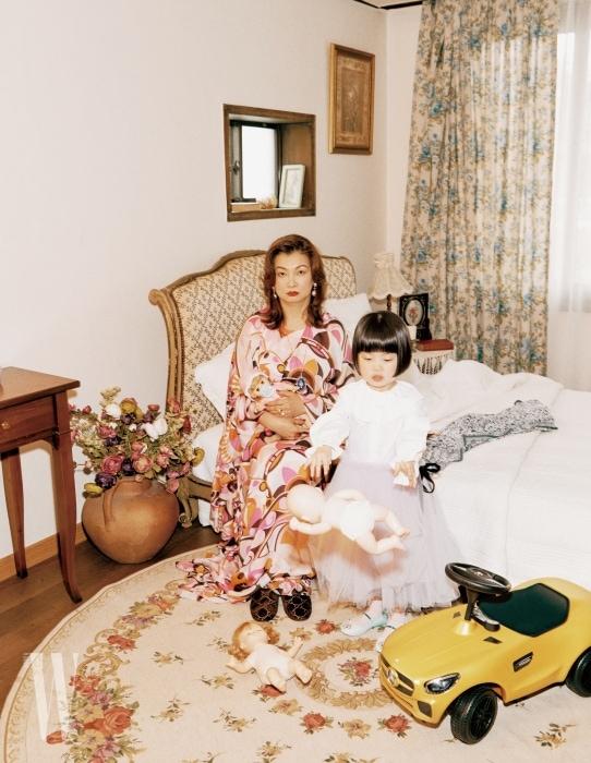 할머니가 착용한 화려한 프린트의 드레스는 Emilio Pucci, 벨벳 슬리퍼는 Gucci, 주얼리는 모두 Tani by Minetani 제품. 손녀가 착용한 흰색 셔츠는 Habille, 연보라색 튤 드레스는 Love., 러버 소재 슈즈는 Native Shoes, 노란색 미니 자동차는 Mercedes-Benz 제품.