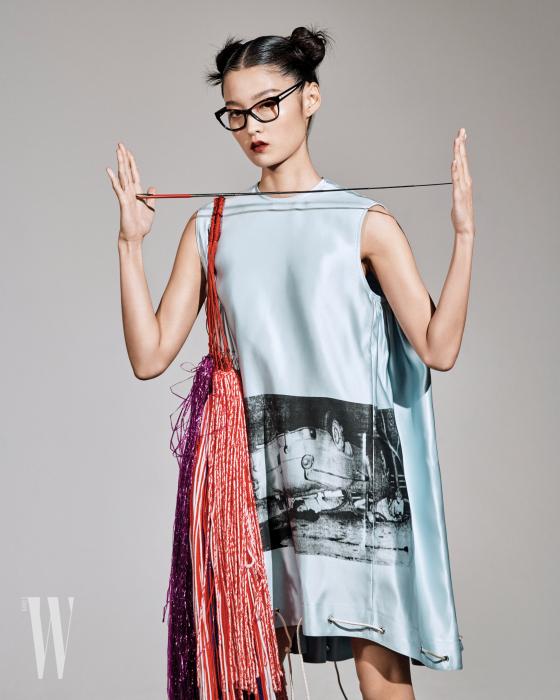 워홀의 흑백 사진을 프린트한 하늘색 새틴 드레스와 큼직한 프린지 백은 캘빈 클라인 205W39NYC 제품. 가격 미정. 캐츠 아이 안경은 샤넬 제품. 가격 미정.