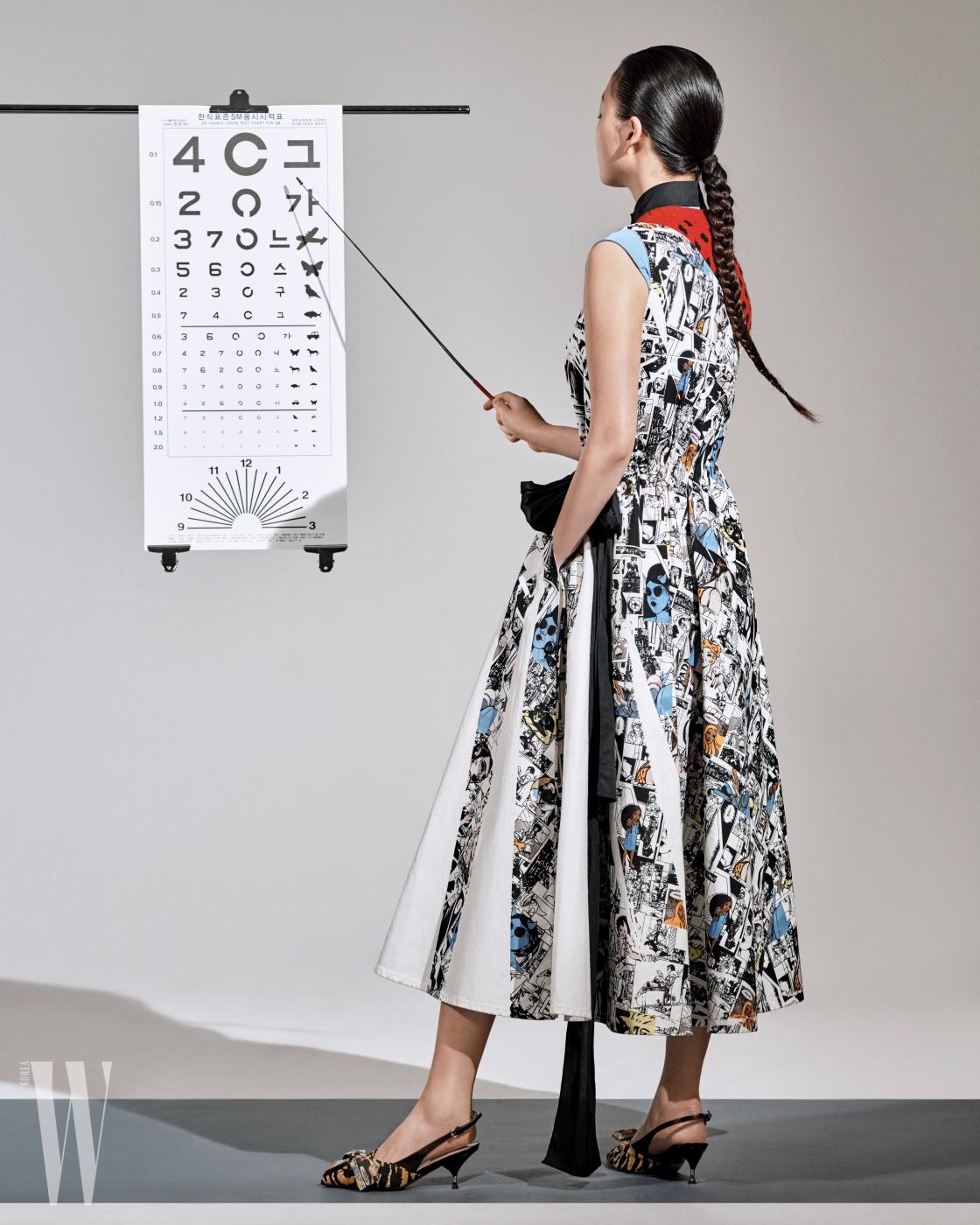 만화 프린트의 오프숄더 드레스, 안에 입은 도트 무늬 베스트와 슬리브리스 셔츠, 애니멀 프린트 슬링백 슈즈는 모두 프라다 제품. 모두 가격 미정.