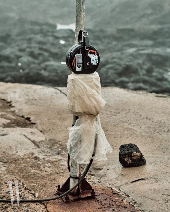 비닐로 덮인 전기 공급기 위에 놓인 동그란 가방은 Louis Vuitton 제품.