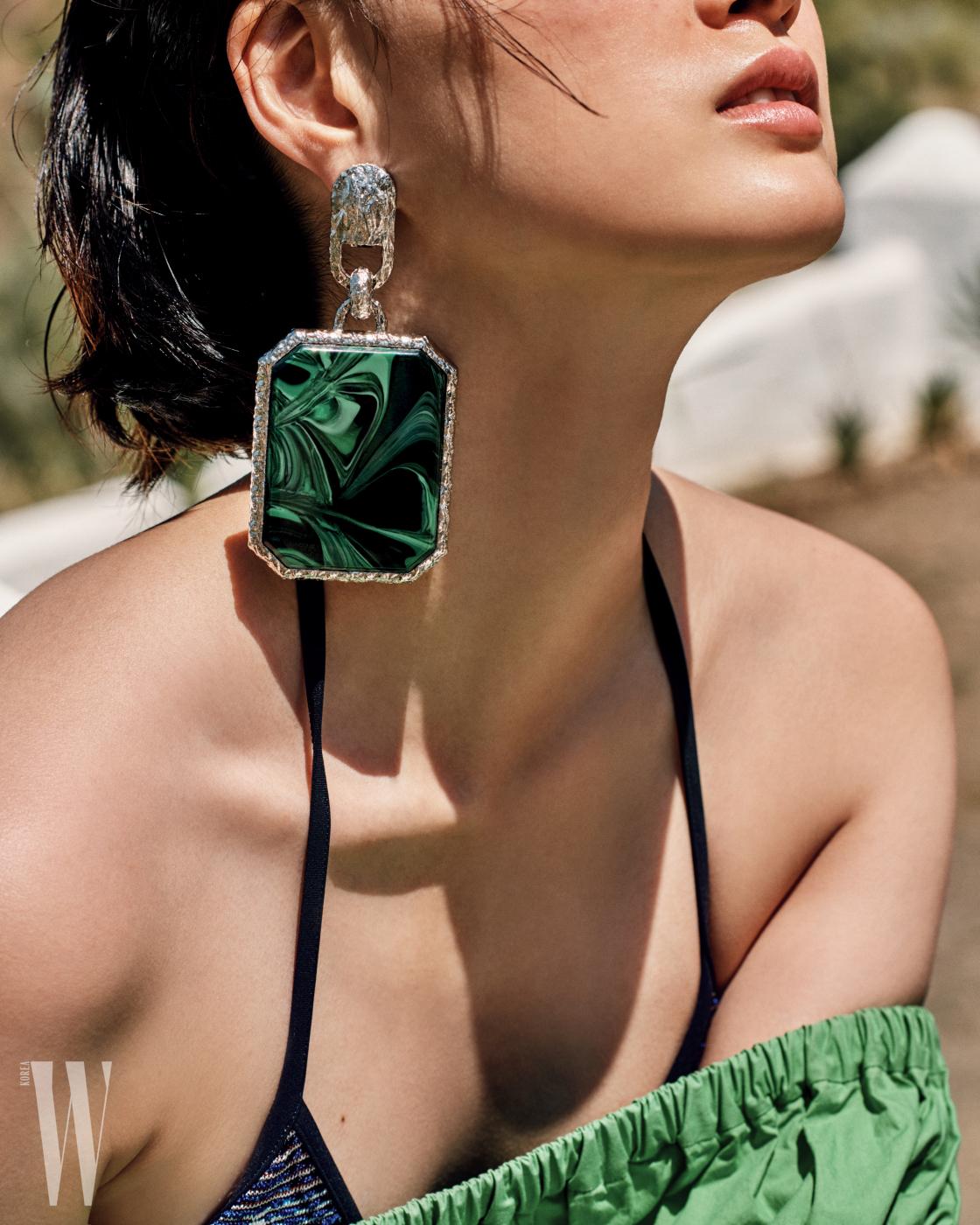 큼지막한 녹색 원석 귀고리는 발렌시아가, 홀터넥 수영복은 미쏘니, 오프숄더 드레스는 포츠 1961 제품.
