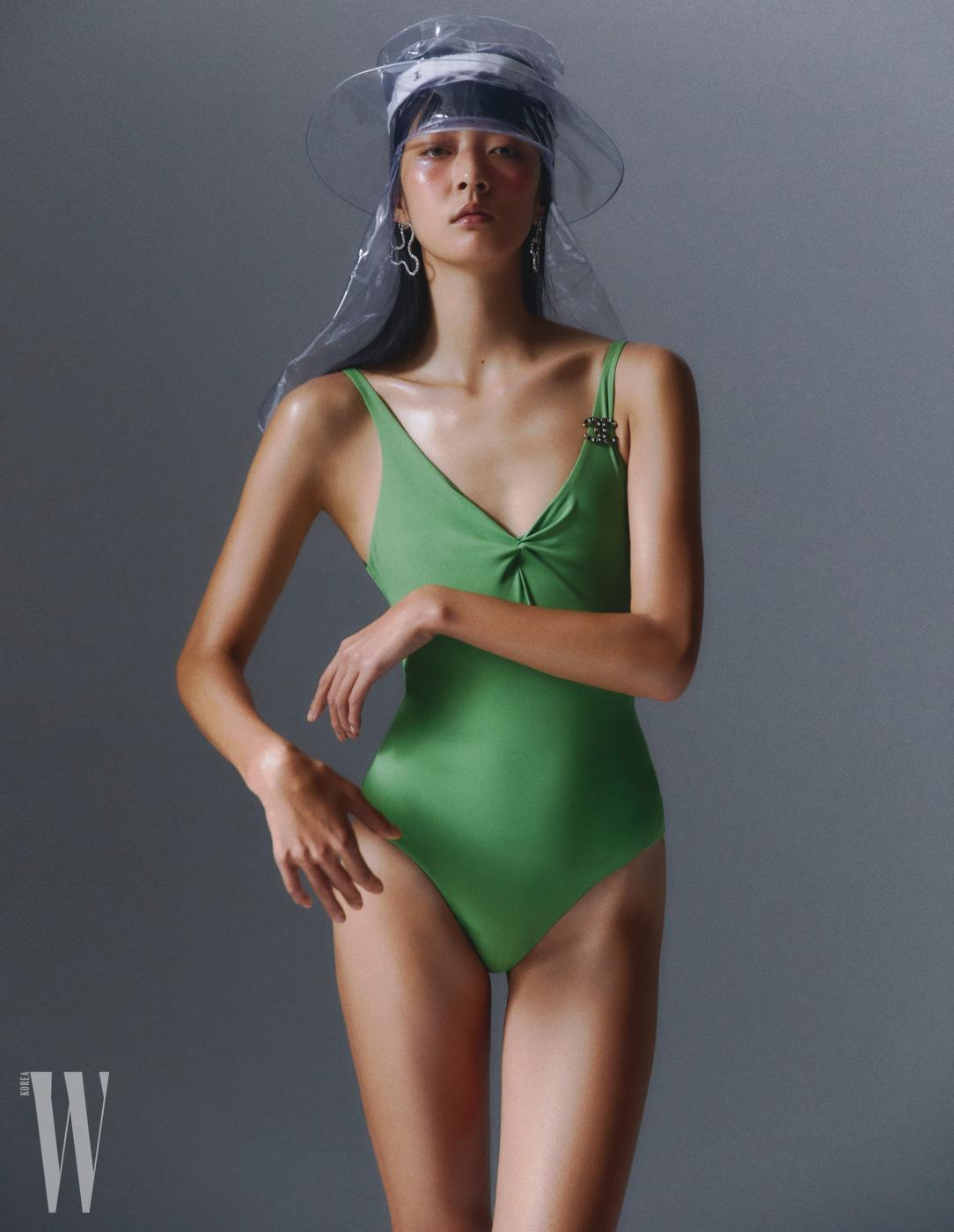 겹쳐서 착용한 PVC 소재 모자, 로고 브로치는 샤넬 제품. 둘 다 가격 미정. 수영복은 코스 제품. 6만9천원. 귀고리는 빈티지 헐리우드 제품. 6만9천원.