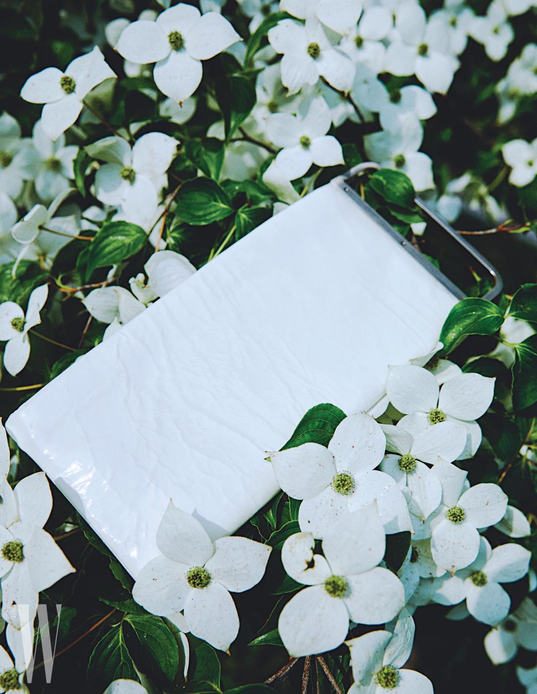 흰색 페이턴트 레더 소재의 직사각형 클러치는 코스 제품.