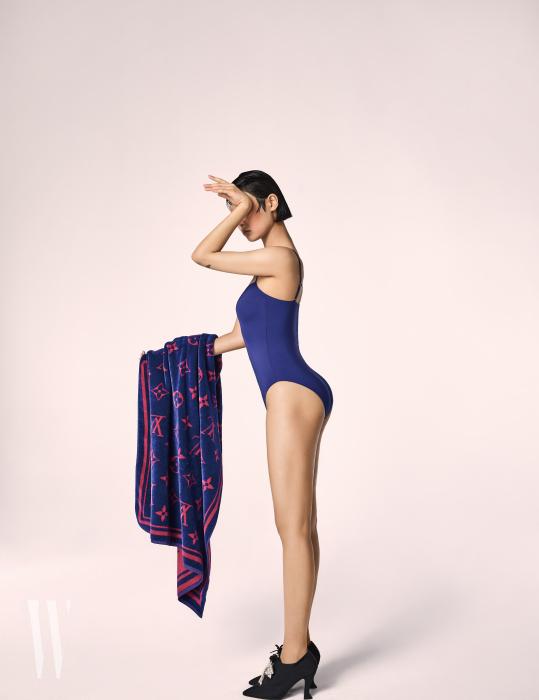 간결한 디자인의 파란색 원피스 수영복은 H&M 제품. 3만5천원. 핑크색 로고 패턴의 비치타월은 루이 비통 제품. 가격 미정. 리본 장식 펌프스는 샤넬 제품. 가격 미정.