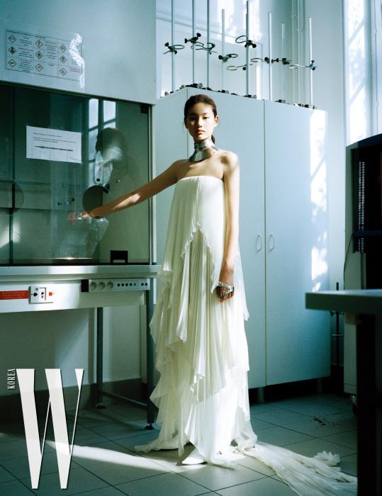 겹겹의주름장식드레스, 강인함이전해지는 메탈소재목걸이와팔찌, 부츠는모두 Givenchy Haute Couture 제품 .
