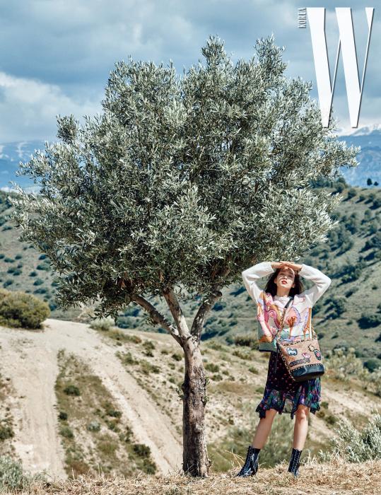 스페인 안달루시아 전역에서 자라는 올리브 나무와 박신혜. 아이보리색니트, 프린트원피스, 검은색레이스업부츠, 패치워크장식더플백은모두Coach 제품.