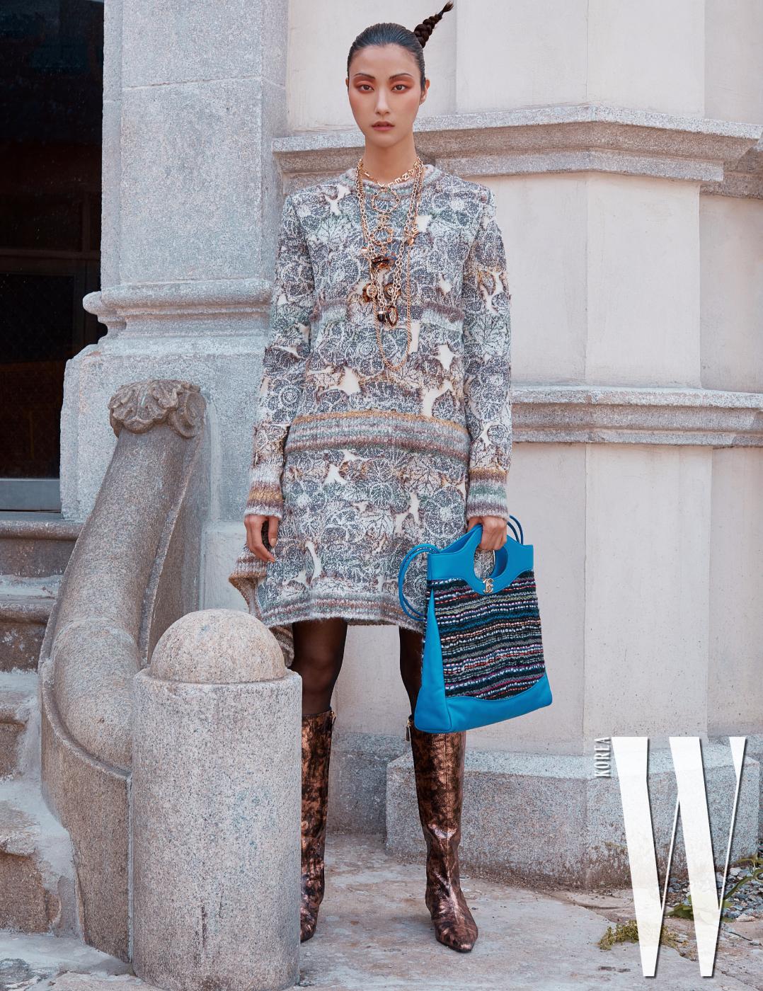 가을 숲이 연상되는 가을 빛깔의 니트 드레스, 쇼퍼백 형태의 '31'백, 부츠, 로고 장식 목걸이와 체인 목걸이, 목에 걸어 착용한 나뭇잎 모티프의 장식이 인상적인 체인 벨트는 모두 Chanel 제품.