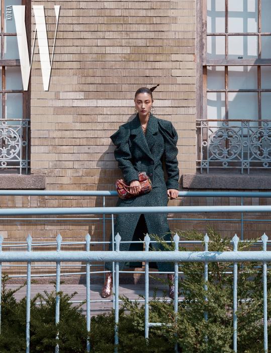 드라마틱한 어깨의 드레이핑이 돋보이는 트위드 롱 코트, 가방, 로고 장식 링 귀고리와 목걸이, 부츠는 모두 Chanel 제품.