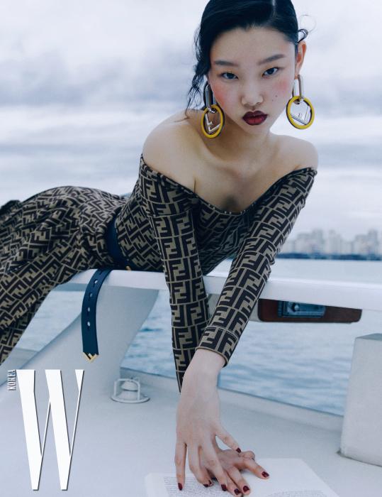 FF 로고 프린트의 오프숄더 드레스, 길게 묶어 연출한 가죽 벨트, 대담한 로고 프레임 귀고리는 모두 Fendi 제품.