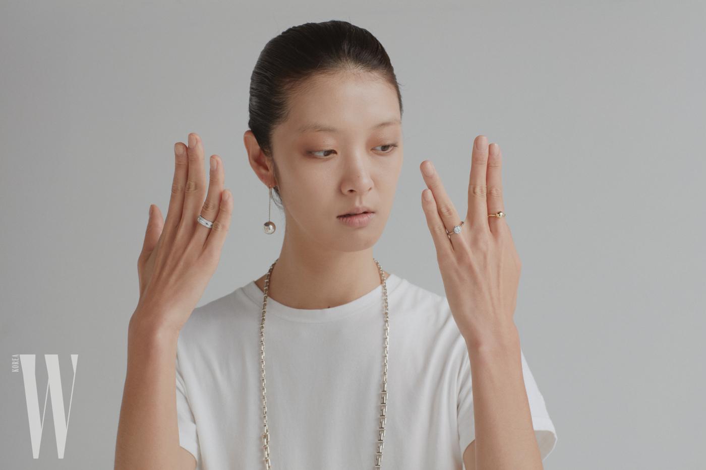 오른쪽 귀에만 싱글 이어링으로 착용한 하드웨어 비드 후크 이어링은 Tiffany & Co. 제품. 심플하고 견고한 디자인의 체인 네크리스는 Tiffany & Co. 제품. 오른손 약지에 착용한 화이트 골드 소재의 파베 다이아몬드 티 투 링은 Tiffany & Co. 제품. 왼손 검지에 착용한 옐로 골드 미니 사이즈 하드웨어 볼 링은 Tiffany & Co. 제품. 왼손 약지에 착용한 플래티넘 소재의 카멜리아 다이아몬드 링은 Chanel Fine Jewelry & Watch 제품.