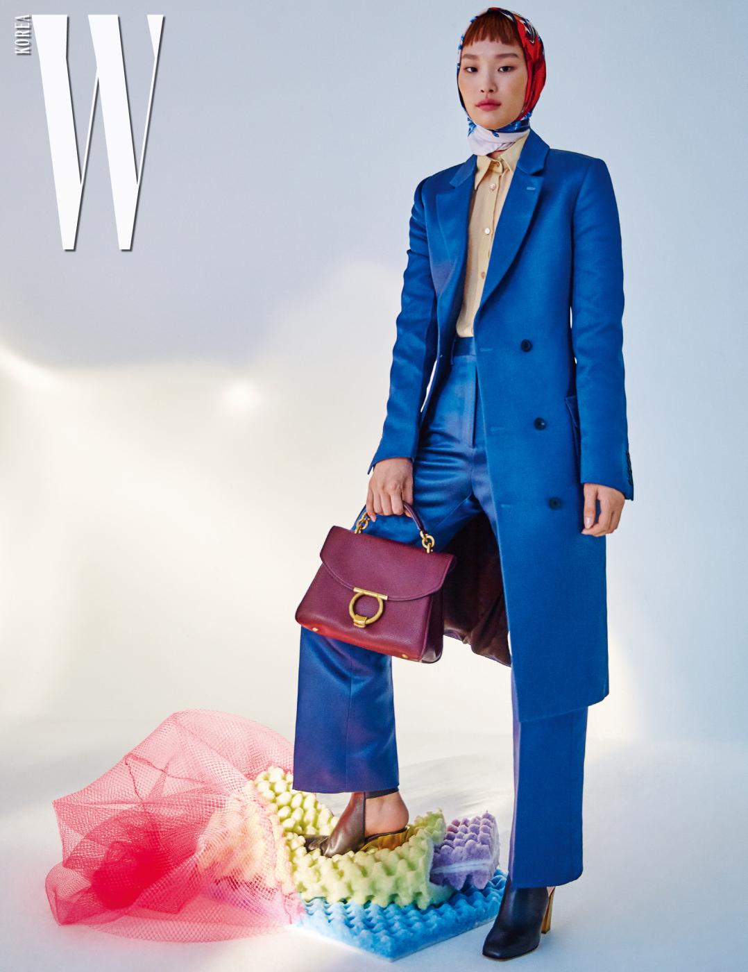 테일러드 슈트, 셔츠, 머리에 둘러 연출한 실크 스카프와 로고 버클 장식 가방은 모두 Salvatore Ferragamo 제품.