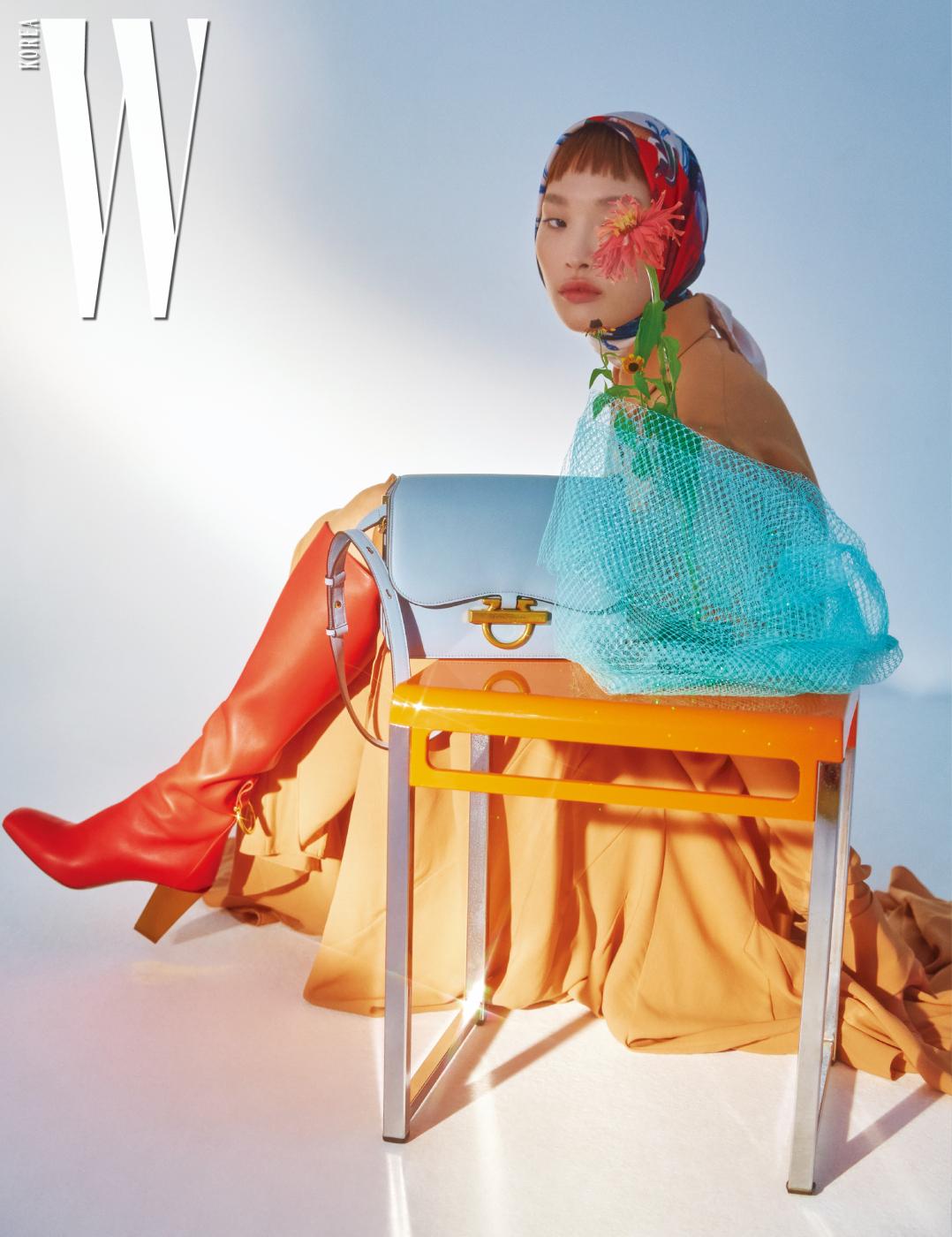 드레스, 실크 스카프, 골드 힐이 특징인 부츠와 파스텔 블루 톤의 클래식한 숄더백은 모두 Salvatore Ferragamo 제품.