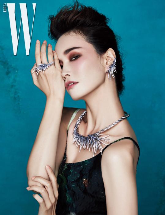 가장무도회의 가면을 모티프로  화이트 골드에 블루 사파이어와  다이아몬드를 화려하게 세팅한  목걸이와 귀고리, 반지는  모두 Tasaki 제품. 신비로운 프린트 드레스는 Prada 제품.
