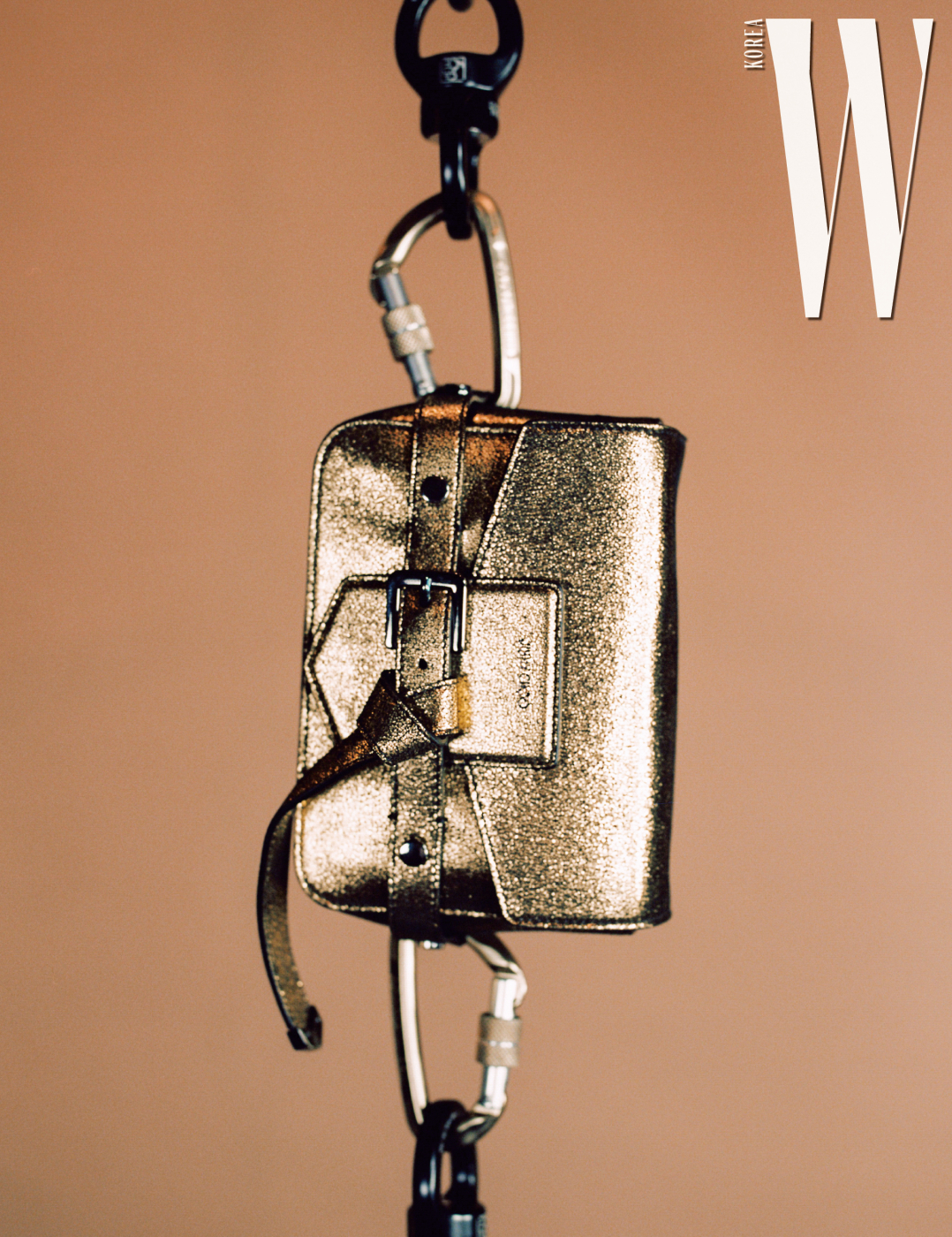 메탈릭한 보 장식 크로스백은 Jimmy Choo 제품.