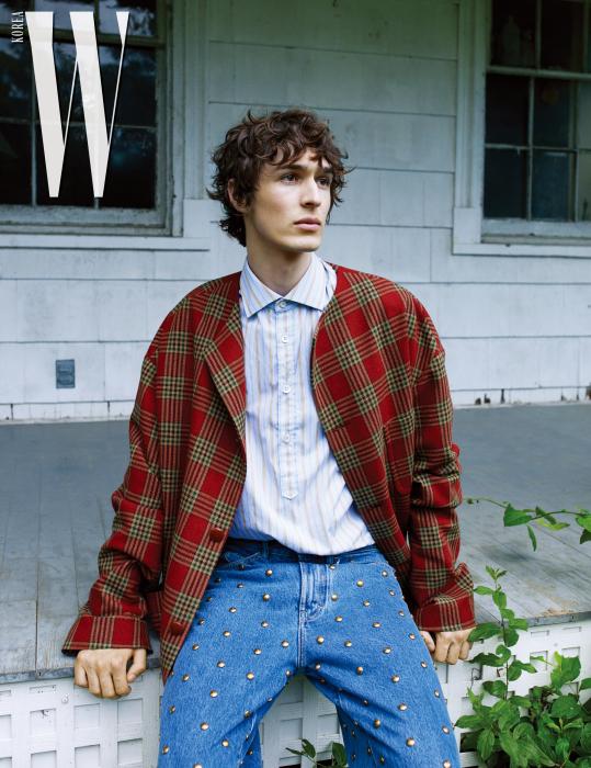 딜런이 착용한 붉은색 체크 울 재킷, 70년대 스타일의 줄무늬 셔츠, 스터드 장식의 푸른색 워싱 데님 팬츠는 모두 Gucci 제품.