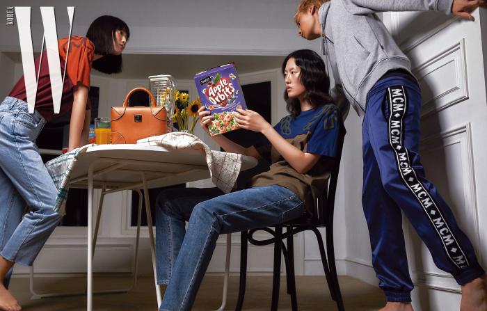 징징유가 입은 컬러 블록 티셔츠, 테이블 위에 놓인 박스형태의 백, 이혜승이 입은 컬러 블록 티셔츠와 데님 팬츠, 주노가 입은 후디 집업과 로고 플레이 트레이닝 팬츠는 모두 MCM 제품.