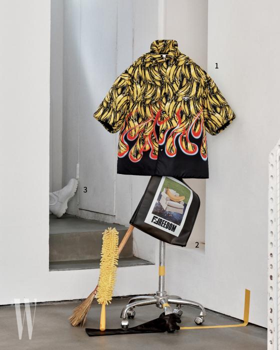 1. 바나나와 불꽃 패턴 셔츠는 프라다 제품. 가격 미정. 2. 사진과 그래픽이 콜라주된 비닐 백은 펜디 제품. 가격 미정. 3. 문 뒤에 놓인 하얀색 워커는 프라다 제품. 가격 미정.