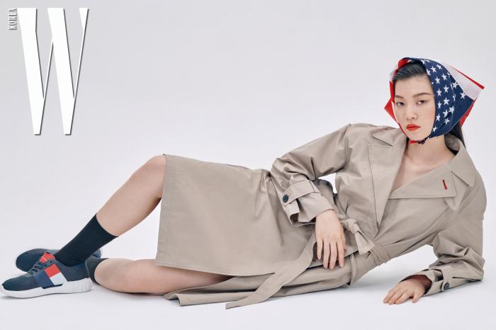 간결한 디자인의 큼직한 에코 트렌치코트, 빅 플래그 경량 메시 스니커즈는 Tommy Hilfiger 제품.