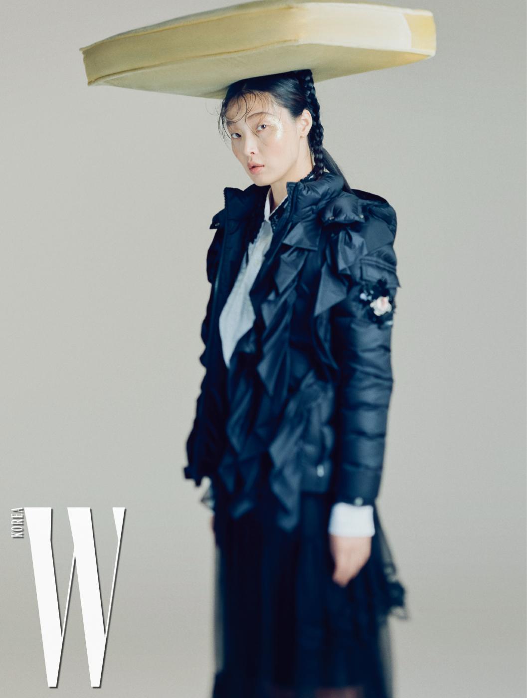 프릴 장식과 꽃으로 둘러진 왼팔의 로고 장식이 독특한 패딩 재킷, 레이스 칼라 장식 셔츠, 시스루 스커트는 모두 4 Moncler Simone Rocha 제품.