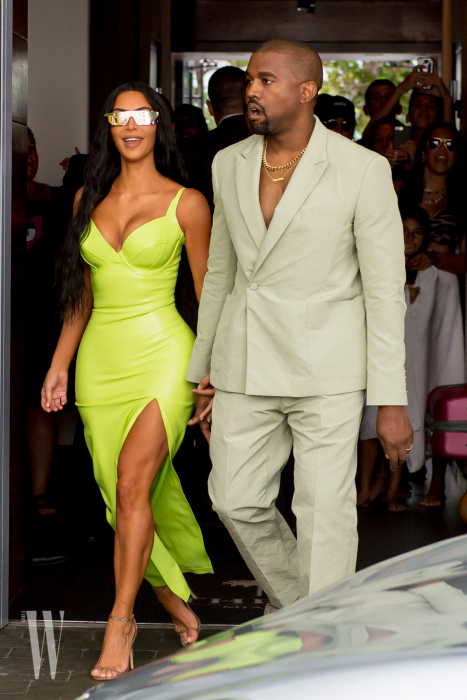 Kim Kardashian turns heads in a neon gown as she and Kanye West arrive at Miami's Versace Mansion for rapper 2Chainz wedding.