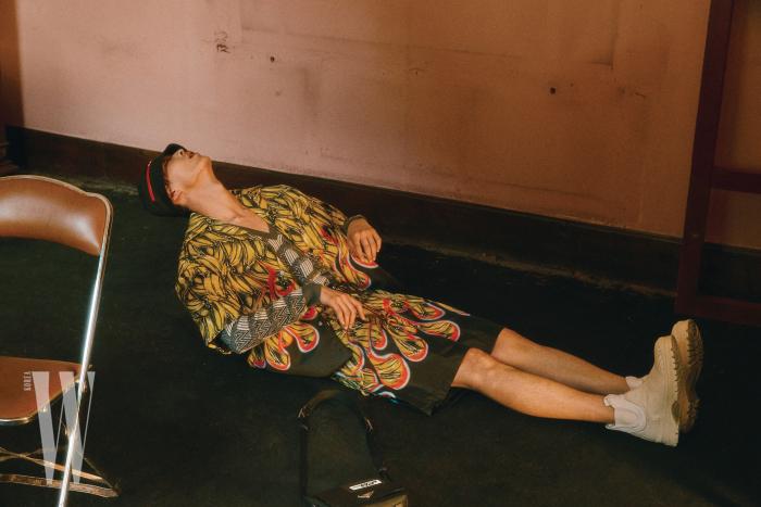 바나나 프린트 셔츠, 쇼츠, 니트 톱, 모자, 부츠, 가방은 모두 Prada 제품.