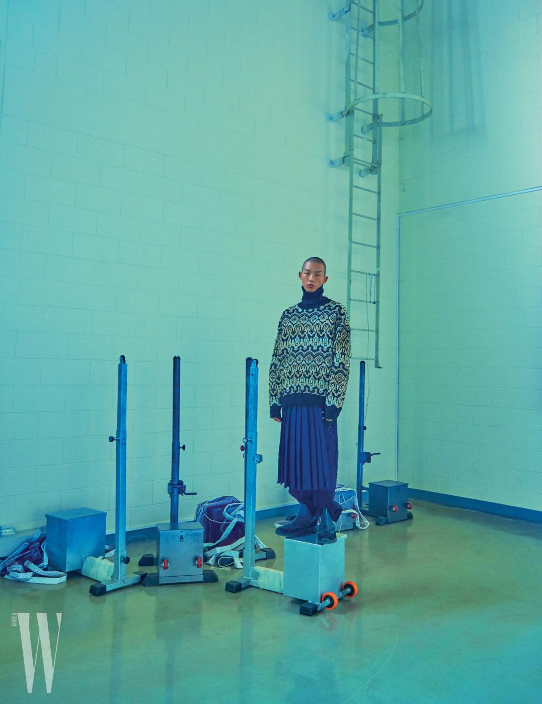 금사와 은사가 섞인 터틀넥과 검은색 아일릿 팬츠, 주름 스커트는 Dries Van Noten by Boon the Shop, 앵클부츠는 Prada 제품.