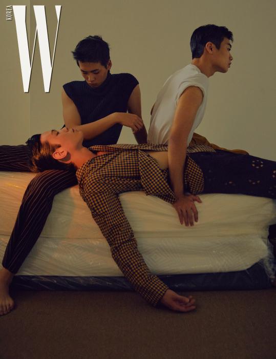 김진곤이 입은 네이비색 터틀넥 니트 베스트는 Dries Van Noten by Boon the Shop, 갈색 줄무늬 팬츠는 Acne Studios 제품. 임지섭이 입은 흰색 티셔츠는 Saint Laurent, 팬츠는 Kimseoryong, 은색 목걸이는 Kantique 1/4 제품. 노신신이 입은 체크 무늬 재킷은 Wooyoungmi, 펀칭 팬츠는 Dries Van Noten 제품.