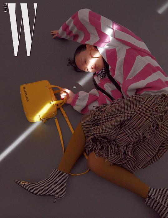 옵아트 패턴의 보 장식 블라우스, 분홍색 줄무늬의 후디 집업 톱, 체크무늬 스커트, 카키색 타이츠, 그래픽 패턴의 앵클부츠, 노란색 가죽 토트백, 귀고리는 모두 Balenciaga 제품.