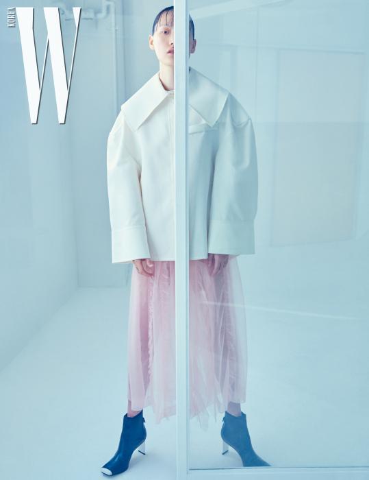 넓은 칼라 장식 재킷은 Jacquemus, 분홍색 시스루 드레스는 4 Moncler Simone Rocha, 건축적인 부츠는 Loewe 제품.