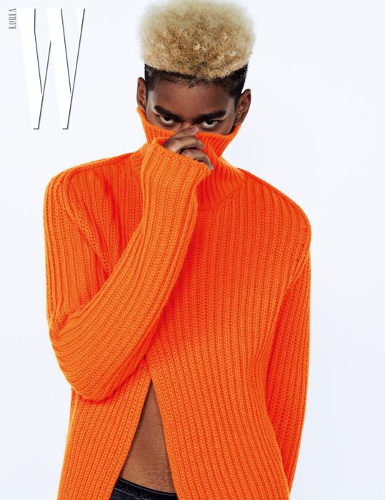 절개가 들어간 오렌지색 터틀넥은 Louis Vuitton 제품.