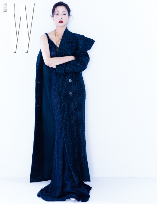 니트 소재의 맥시 드레스는 Max Mara, 어깨를 봉긋하게 강조한 실루엣이 돋보이는 트위드 코트와 목걸이는 모두 Chanel, 흰색 펌프스는 Jimmy Choo 제품.