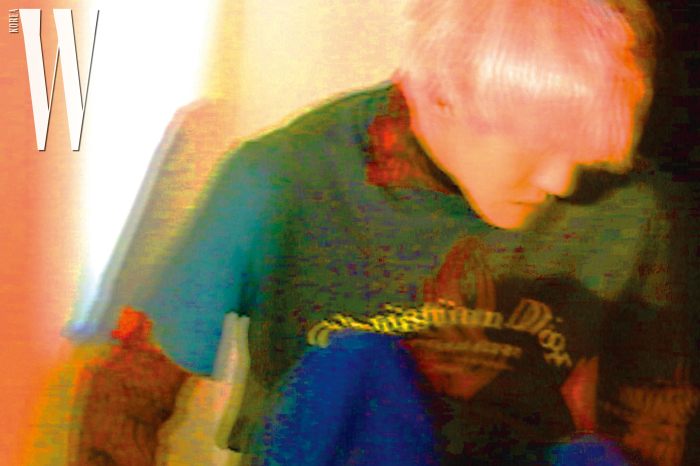 카키색 티셔츠와 안에 입은 패턴 셔츠, 넉넉한 핏의 데님 팬츠는 Dior Homme 제품.