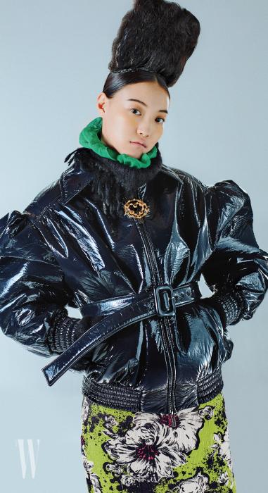 반짝이는 질감의 오버사이즈 재킷, 초록색 스카프, 꽃무늬 스커트는 미우미우 제품, 목걸이는 샤넬 제품.