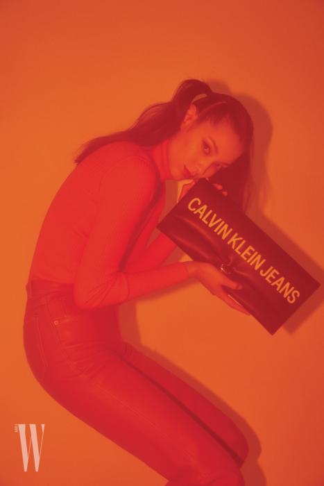 터틀넥 톱, 클러치는 Calvin Klein Jeans, 가죽 팬츠는 Gucci 제품.