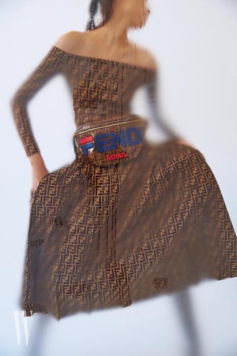 F 로고로 뒤덮인 오프숄더 드레스, 펜디 마니아 벨 파우치, 부츠는 모두 Fendi 제품.