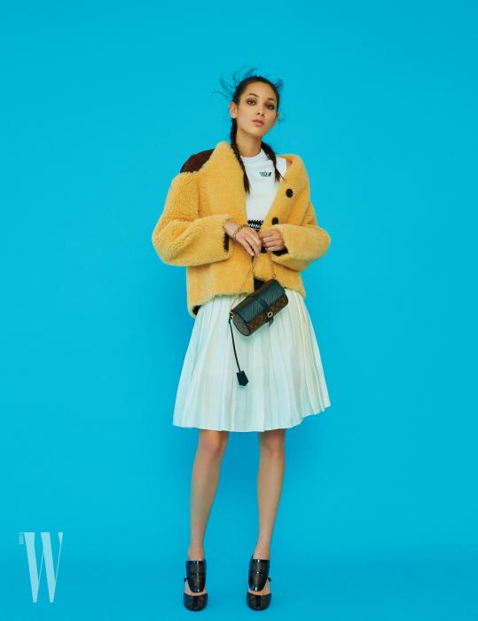 셔링 재킷, 톱, 주름 스커트, 로고 장식 가방과 슈즈는 모두 Louis Vuitton 제품.