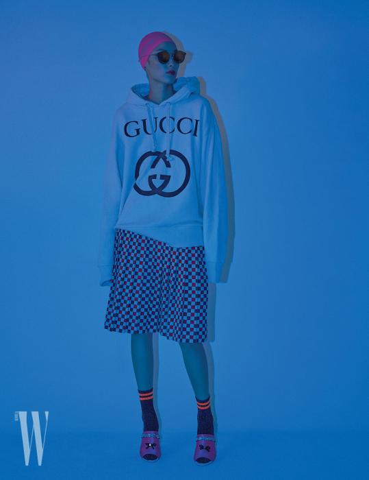 로고 프린트 후디, 스커트는 Gucci, 핑크 새틴 슈즈는 Stuart Weitzman, 선글라스는 Paul Hueman 제품.