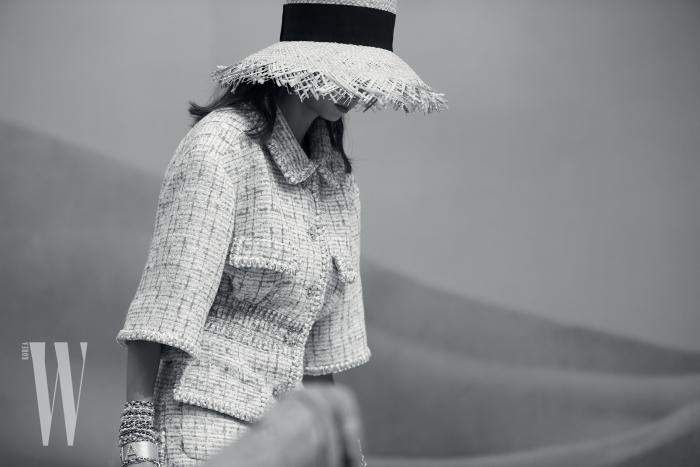 큼직한 라피아 모자, 단아한 트위드 슈트. 샤넬이 제안한 부르주아식 리조트 룩은 바로 이런 것.